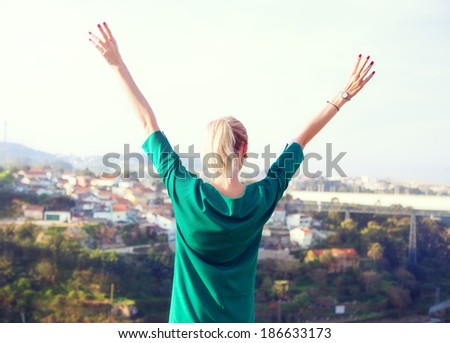 Happy blonde woman looking at city landscape of Porto. - stock photo