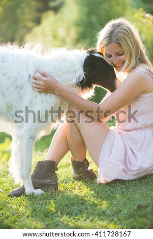 Happy blonde woman playing with her Russian wolfhound dog in garden - stock photo