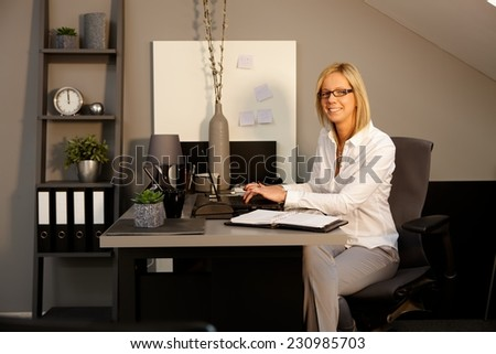 Happy blonde woman sitting at desk in office, working with laptop computer, smiling, looking at camera. - stock photo