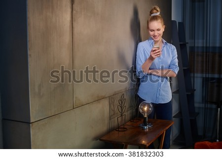 Happy blonde woman standing by wall at home, reading text message, holding mobilephone, smiling. - stock photo
