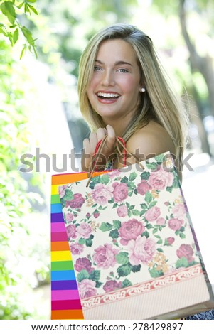 Happy blonde young woman smiling with shopping bags - stock photo