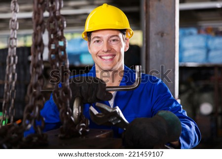 happy blue collar worker with tools in workshop - stock photo