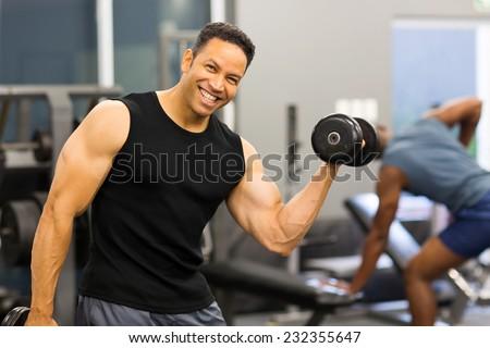 happy bodybuilder lifting dumbbells in gym - stock photo