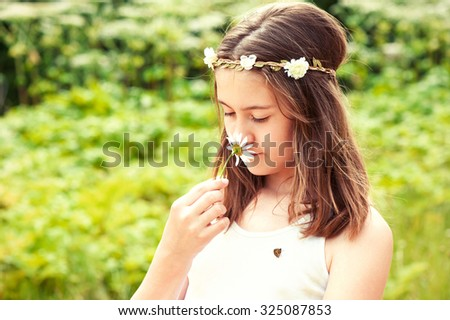 Happy boho style cheerful girl with floral headband on head and butterfly smelling camomile. Summertime multicolored outdoors horizontal image. - stock photo