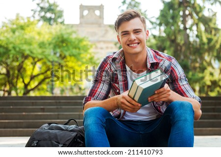 Happy bookworm. Handsome male student holding textbooks and smiling while sitting at the outdoors staircase with university building in the background - stock photo