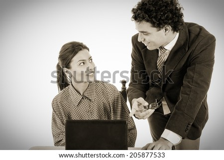 happy Boss and smiling secretary working together on laptop computer, showing something on screen, black and white style - stock photo