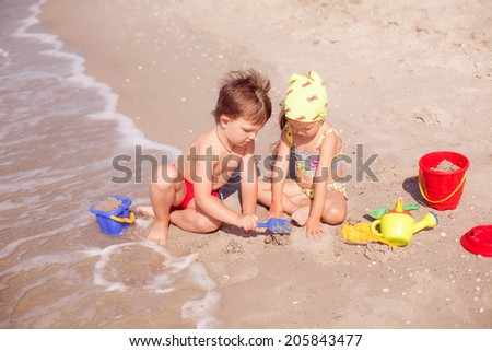 happy boy and girl playing in the sand on the seashore - stock photo