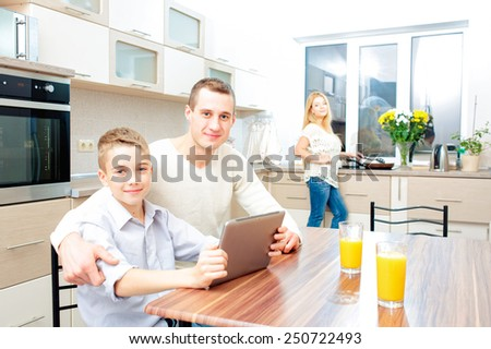 Happy boy and his father looking at the camera with a digital tablet while mother cooking dinner in kitchen - stock photo