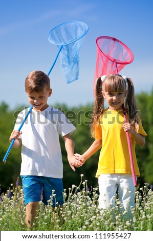 Happy boy and little girl with butterfly nets walking on a meadow in a sunny day - stock photo