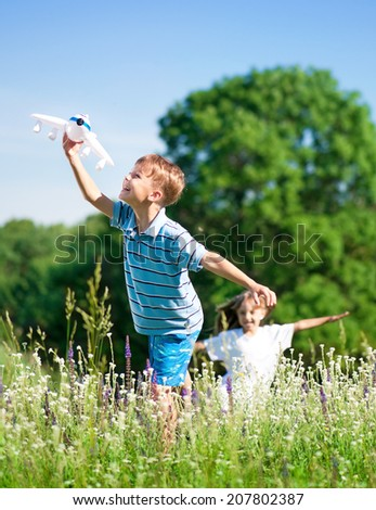 Happy boy and little girl with plane on a meadow in a sunny day - stock photo