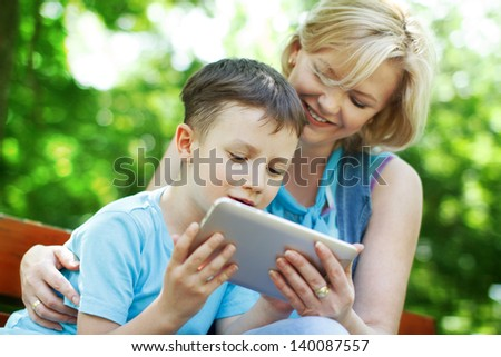 Happy boy and mother with tablet, outdoor - stock photo