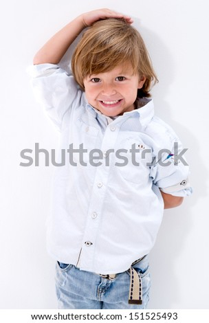 Happy boy checking his height agaisnt the wall  - stock photo