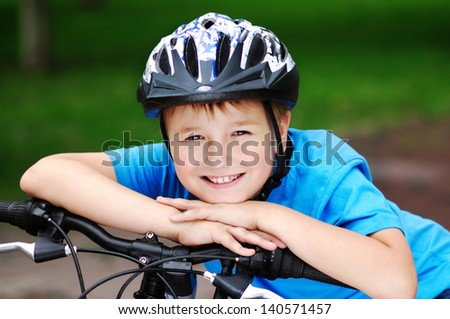 happy boy cyclist holding hands on his bicycle handlebar - stock photo