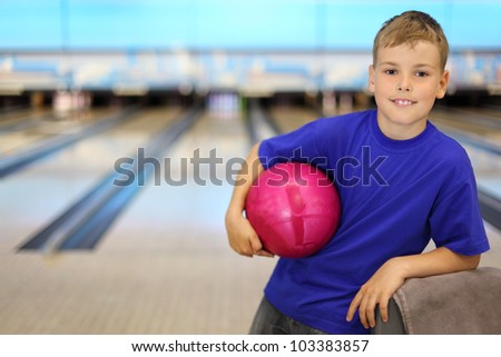 Happy boy dressed in blue T-shirt holds pink ball in bowling club; shallow depth of field - stock photo