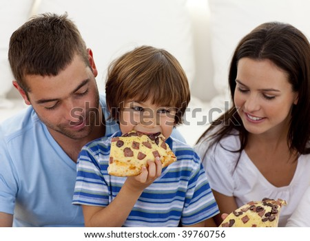 Happy boy eating pizza with ihs parents in living-room - stock photo