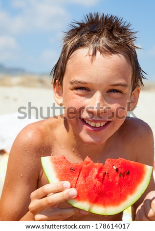 Happy boy eating watermelon on a beach - stock photo