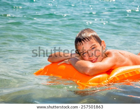 Happy boy enjoying summer day floating in the sea - stock photo