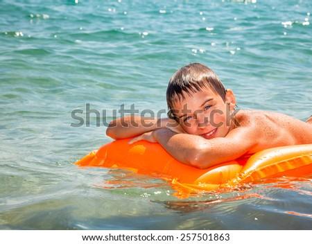 Happy boy enjoying summer day floating in the sea - stock photo