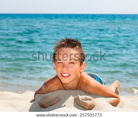 Happy boy enjoying summer day on a beach - stock photo