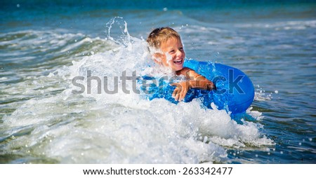 happy boy enjoying swimming in the sea with rubber ring - stock photo