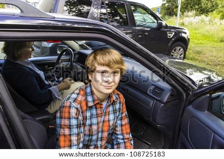 happy boy entering the car - stock photo