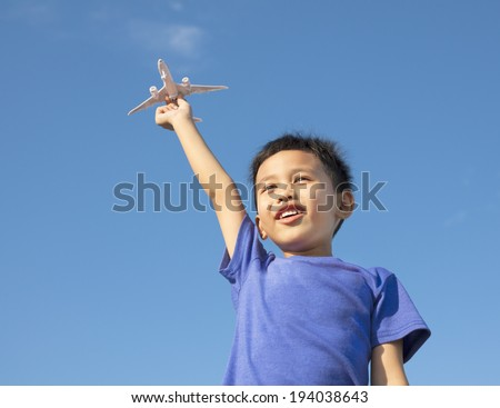 happy boy holding a airplane toy with blue sky - stock photo