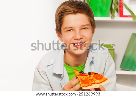 Happy boy holding pizza piece and eating at home - stock photo