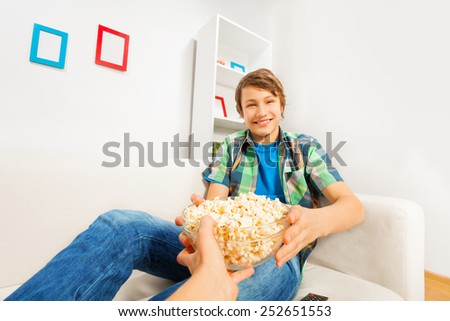 Happy boy holds popcorn bowl from someone's hand - stock photo