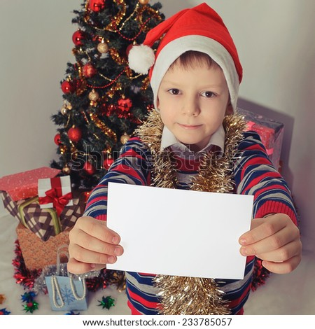 Happy boy in Santa red hat holding Christmas greeting blank card in hands. Christmas concept. Selective focus - stock photo