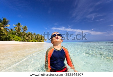 happy boy in swimming goggles on beach - stock photo