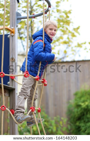 Happy boy in warm blue bright coat having fun at the playground climbing on the net on a winter, late autumn or early spring day - stock photo