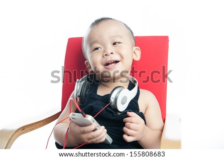 happy boy listening to music on headphones against white - stock photo