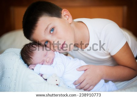 Happy boy next to her newborn brother - stock photo