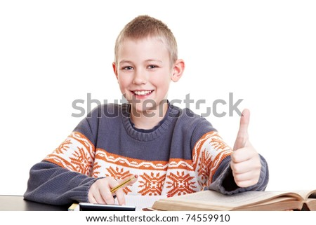 Happy boy on his desk with homework holding his thumb up - stock photo