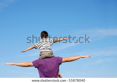 Happy boy on mans shoulders - stock photo