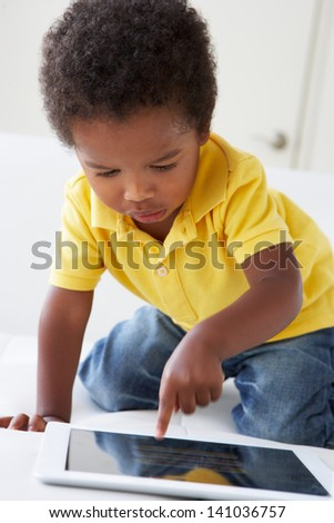 Happy Boy On Sofa Playing With Digital Tablet - stock photo