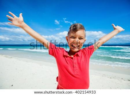 Happy boy on the beach - stock photo