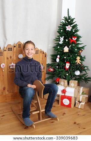 Happy boy on the wooden horse near Christmas tree - stock photo