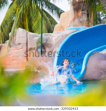 Happy boy on water slide in a swimming pool having fun during summer vacation in a beautiful tropical resort - stock photo