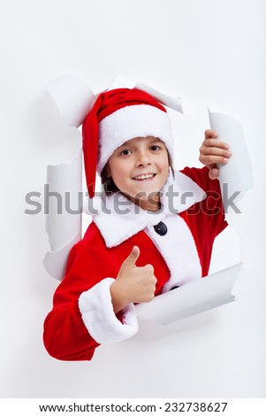 Happy boy opening christmas season - widening a hole in white paper layer - stock photo