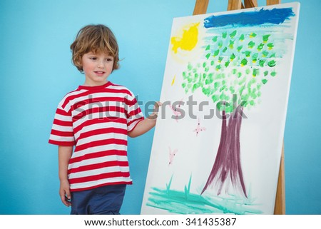 Happy boy painting his picture on an easel - stock photo