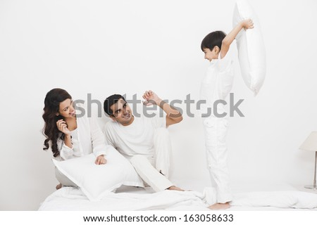 Happy boy pillow fight with his parents on the bed - stock photo