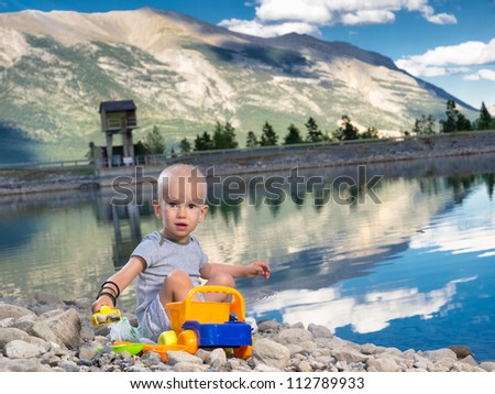 Happy boy playing at the lake in Canmore, Banff, Alberta. Hair loss due to strong Chemo therapy regimen. - stock photo
