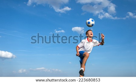 happy boy playing football on sky background - stock photo