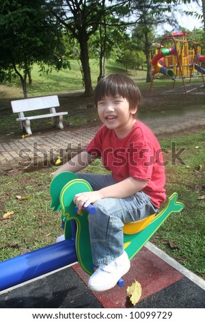 Happy boy playing seesaw at the playground in the park - stock photo