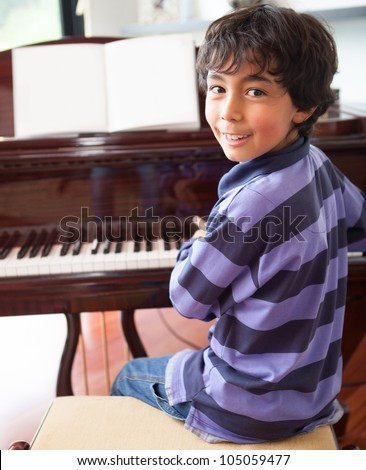 Happy boy playing the piano at home - stock photo