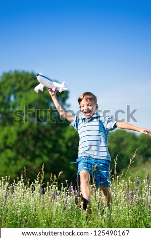 Happy boy playing with a toy plane on a meadow in a sunny day - stock photo