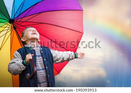 Happy boy portrait with bright rainbow umbrella - stock photo