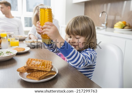 Happy boy pouring honey on waffles while having breakfast with family - stock photo