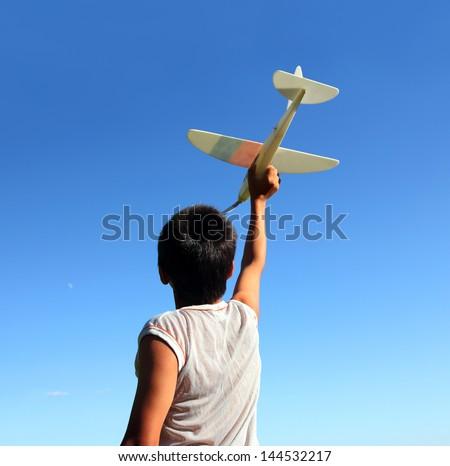 happy boy running airplane model under blue sky - stock photo